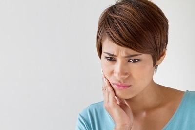 Woman holding jaw in pain | Dentist Glendale CA