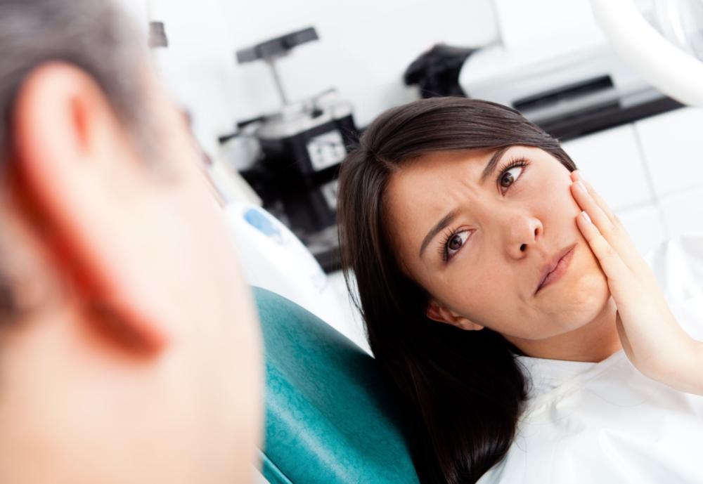 Woman holding jaw from pain | Dentist Glendale CA