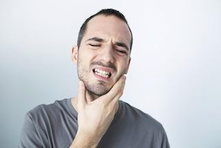 Man expereincing jaw pain who needs to see a dentist in Glendale CA