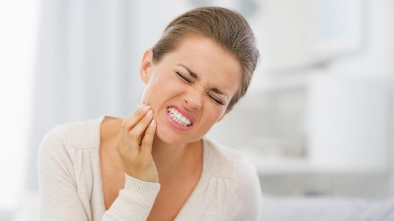 Woman holding jaw in pain | Dental Emergency Treatment in Glendale