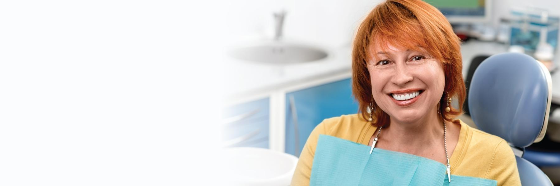 Woman with red hair smiling in a dental exam room
